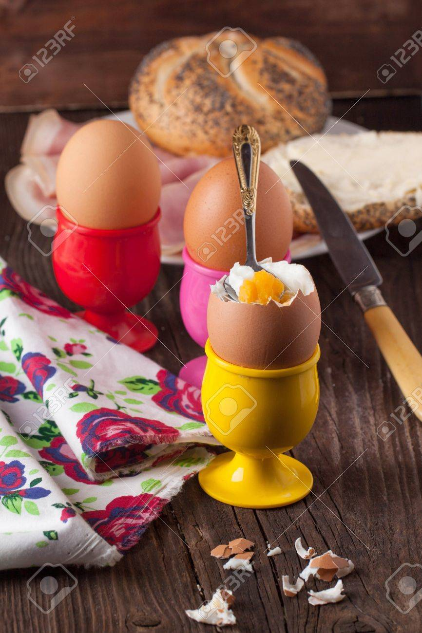 peeled boiled eggs in colorful cups and textile on wooden table Stock Photo - 18558492