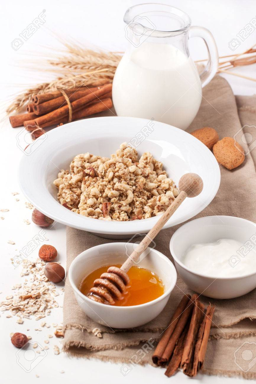 Plate of muesli with milk, honey, cinnamon and nuts over white. See series - 23999416