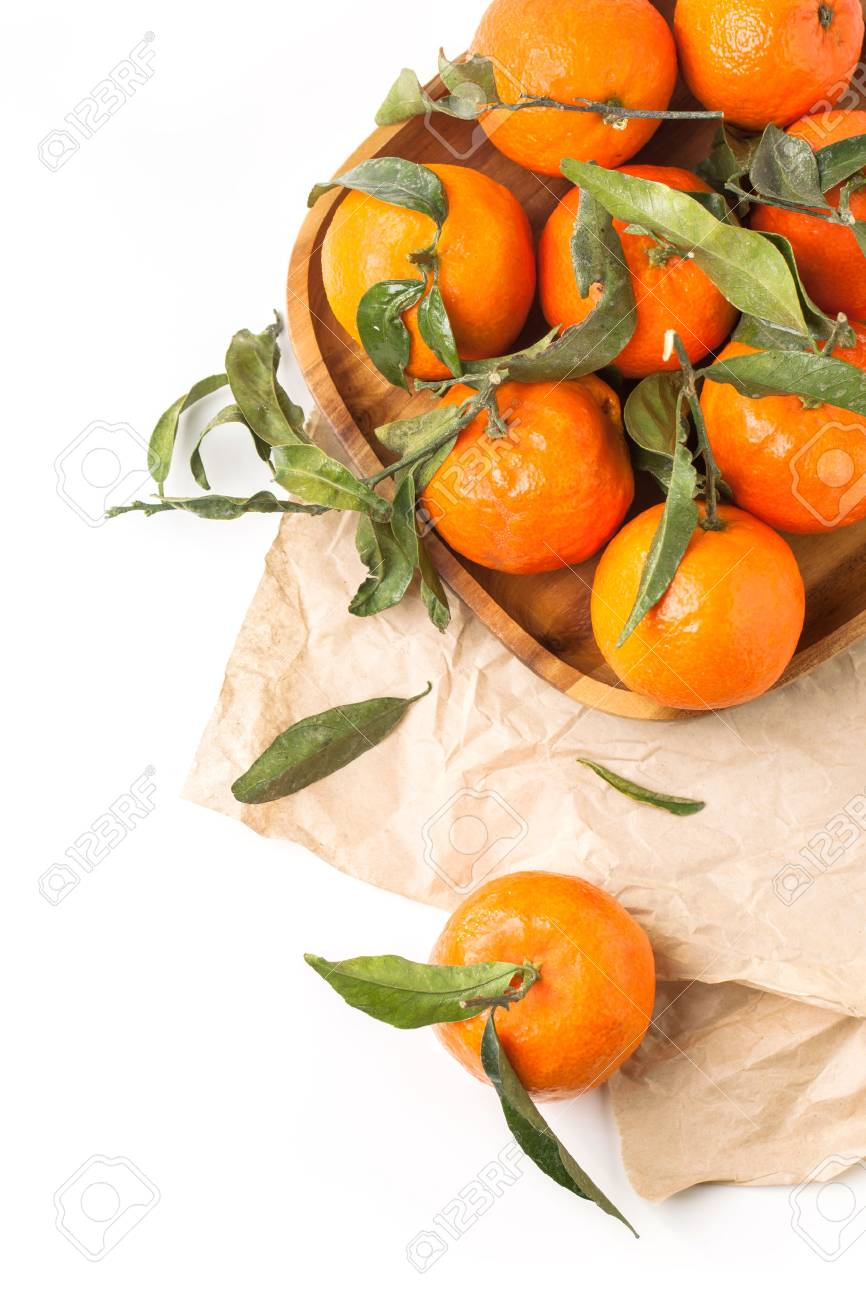 Top view on wooden plate of tangerines with leaves on crumpled paper over white - 25103045