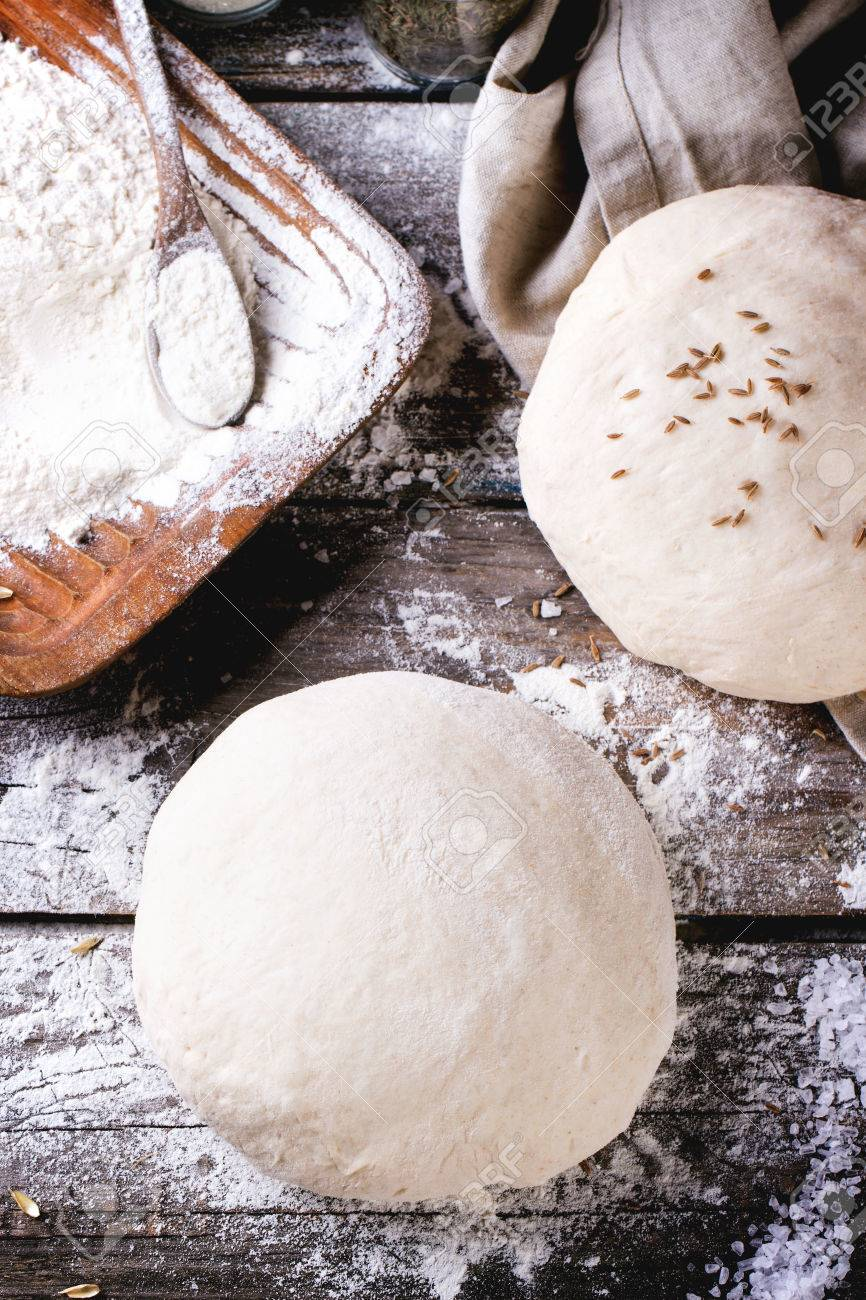 Baking bread. Dough on wooden table with flour, rolling-pin and jars with backing ingredients. Top view. See series - 30481902