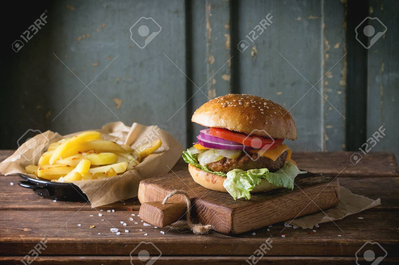 Fresh homemade burger on little cutting board with grilled potatoes, served with ketchup sauce and sea salt over wooden table with gray wooden background. Dark rustic style. - 42285644