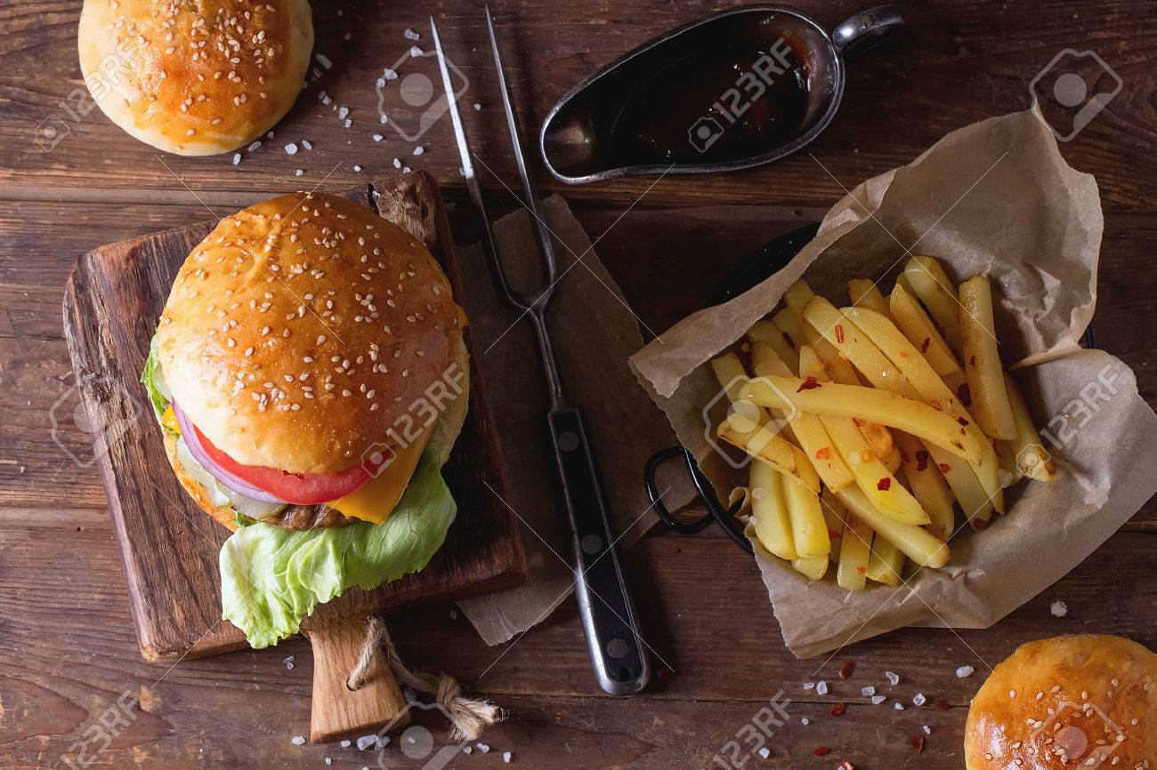 Fresh homemade burger on little cutting board with grilled potatoes, served with ketchup sauce and meat fork over wooden table. Dark rustic style. Top view - 42284785
