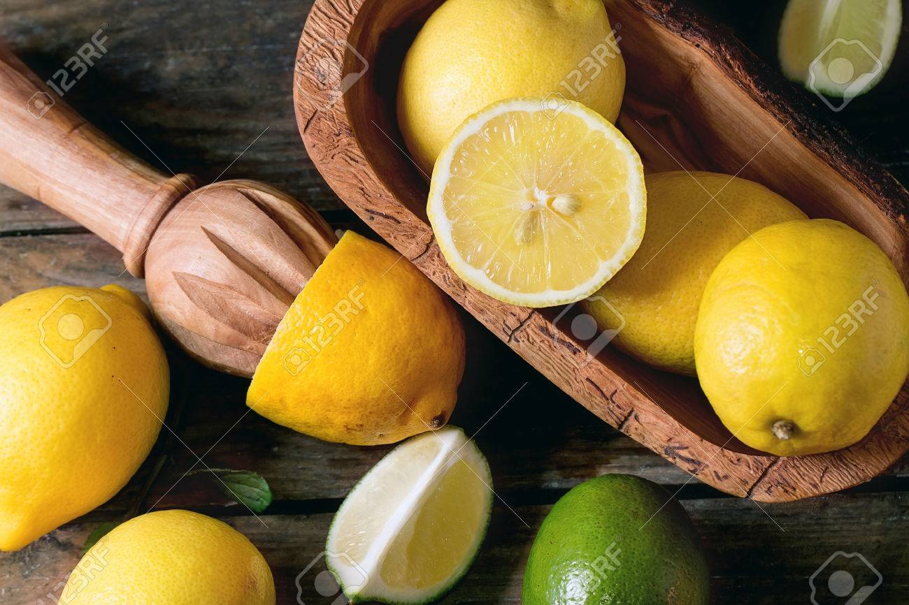 Heap of whole and sliced lemons and limes in olive wood bowl and citrus reamer over wooden background. Top view - 42284686