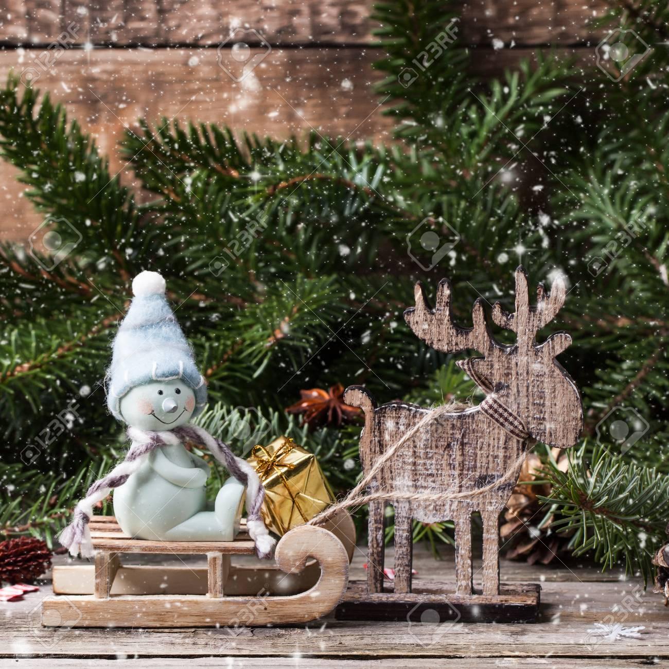 Regali Di Natale In Legno.Cartolina Di Natale Con Il Pupazzo Di Neve Sulla Slitta Cervo In Legno E Regali Di Natale Piu Vecchio Fondo In Legno Con La Neve Che Cade Immagine