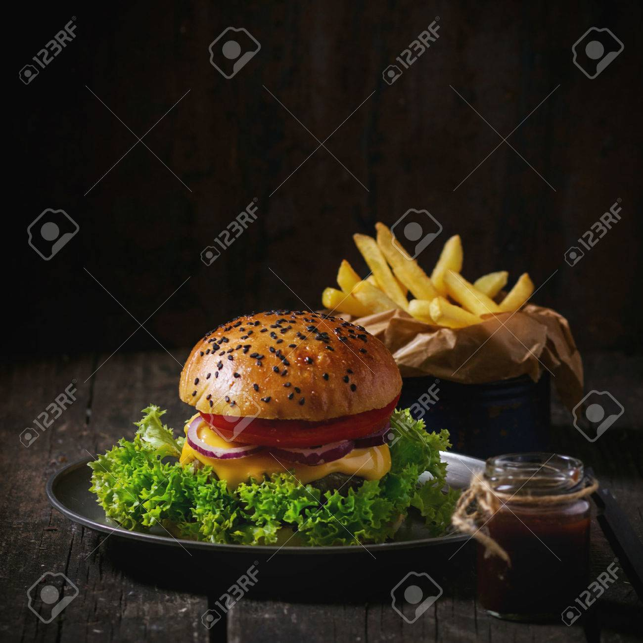 Fresh homemade hamburger with black sesame seeds in old metal plate with fried potatoes, served with ketchup sauce in glass jar over old wooden table with dark background. Dark rustic style. Square image - 51951880