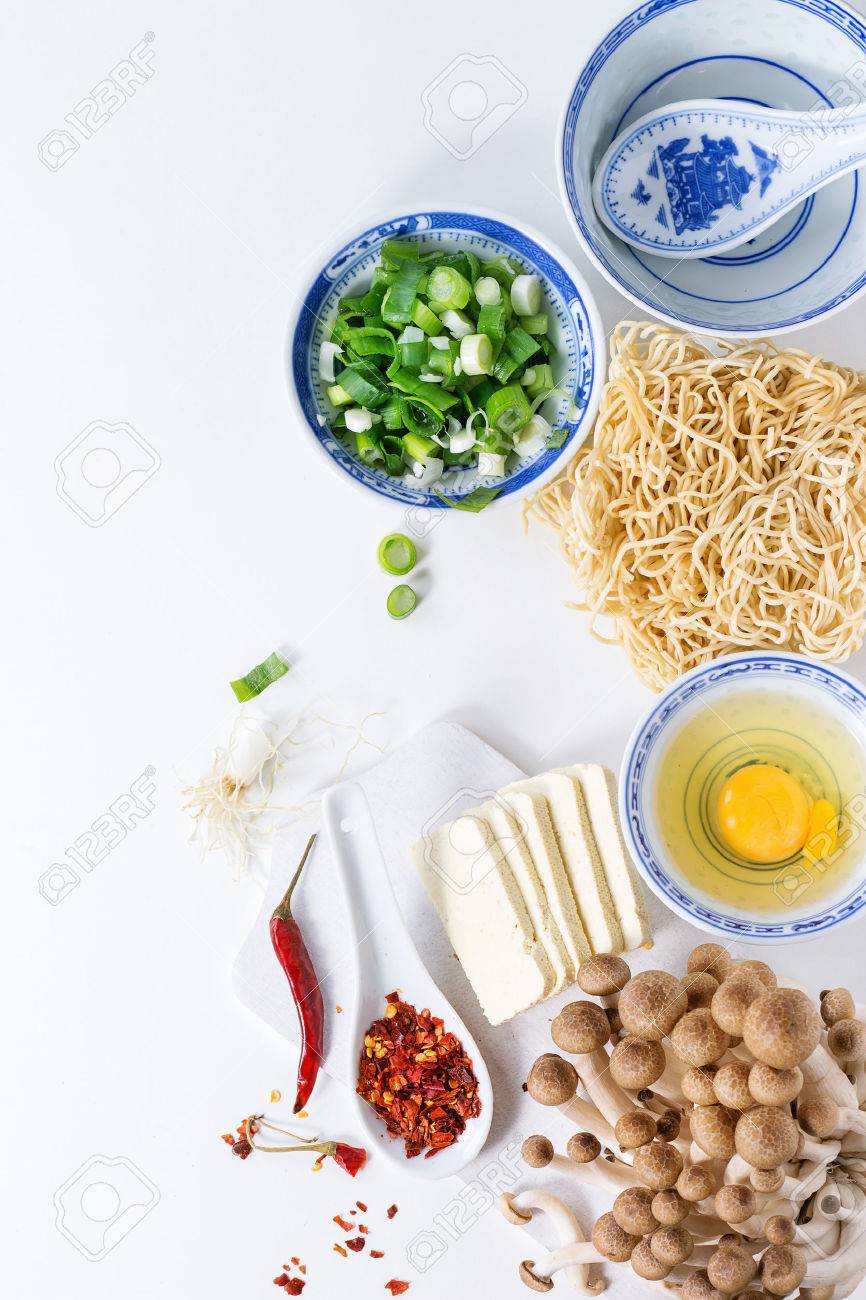 Ingredients for asian ramen soup. Noodles, spring onion, feta cheese, mushrooms, egg and chili pepper in asian porcelan bowls over white kitchen table. Top view - 52572274