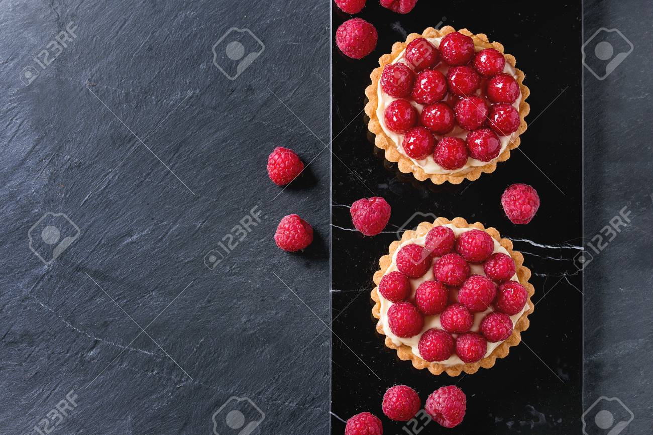 Two Tartlets with custard and fresh ripe raspberries, served on black marble board over stone slate surface. With copy space at left. Top view - 53823666