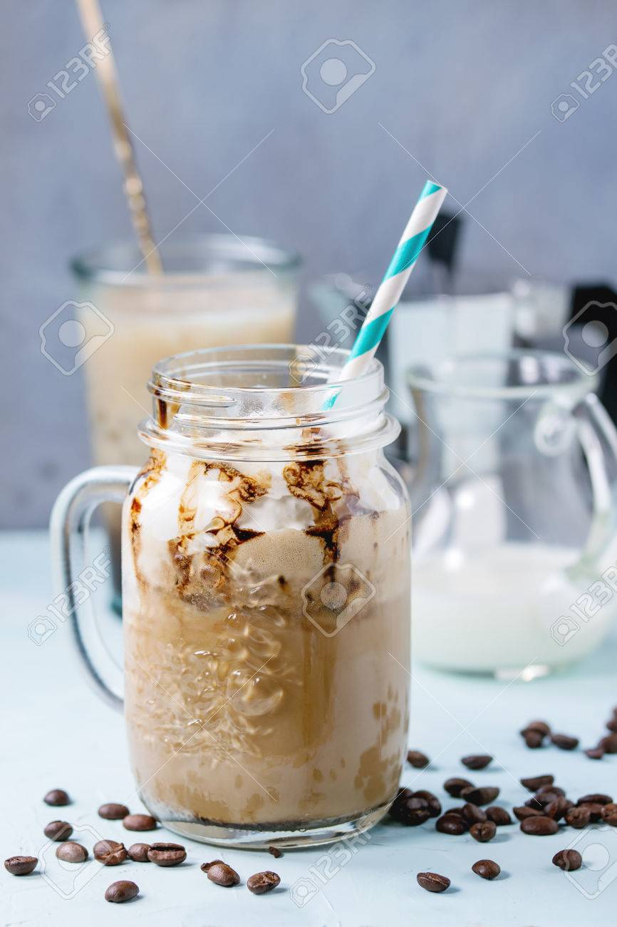 Glass mason jar with ice coffee with whipped cream, ice cream and chocolate sauce, served with coffee beans, coffe pot and jug of milk over light blue textured background. - 55782631