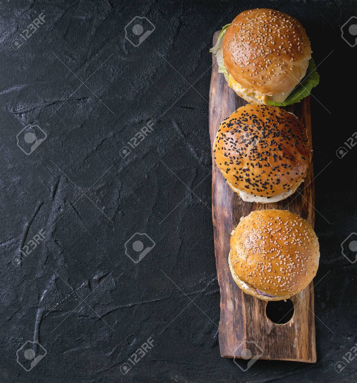 Three Homemade veggie burgers with sweet potato, black rice and red beans, served on wooden chopping board over black textured background. Top view - 55782672