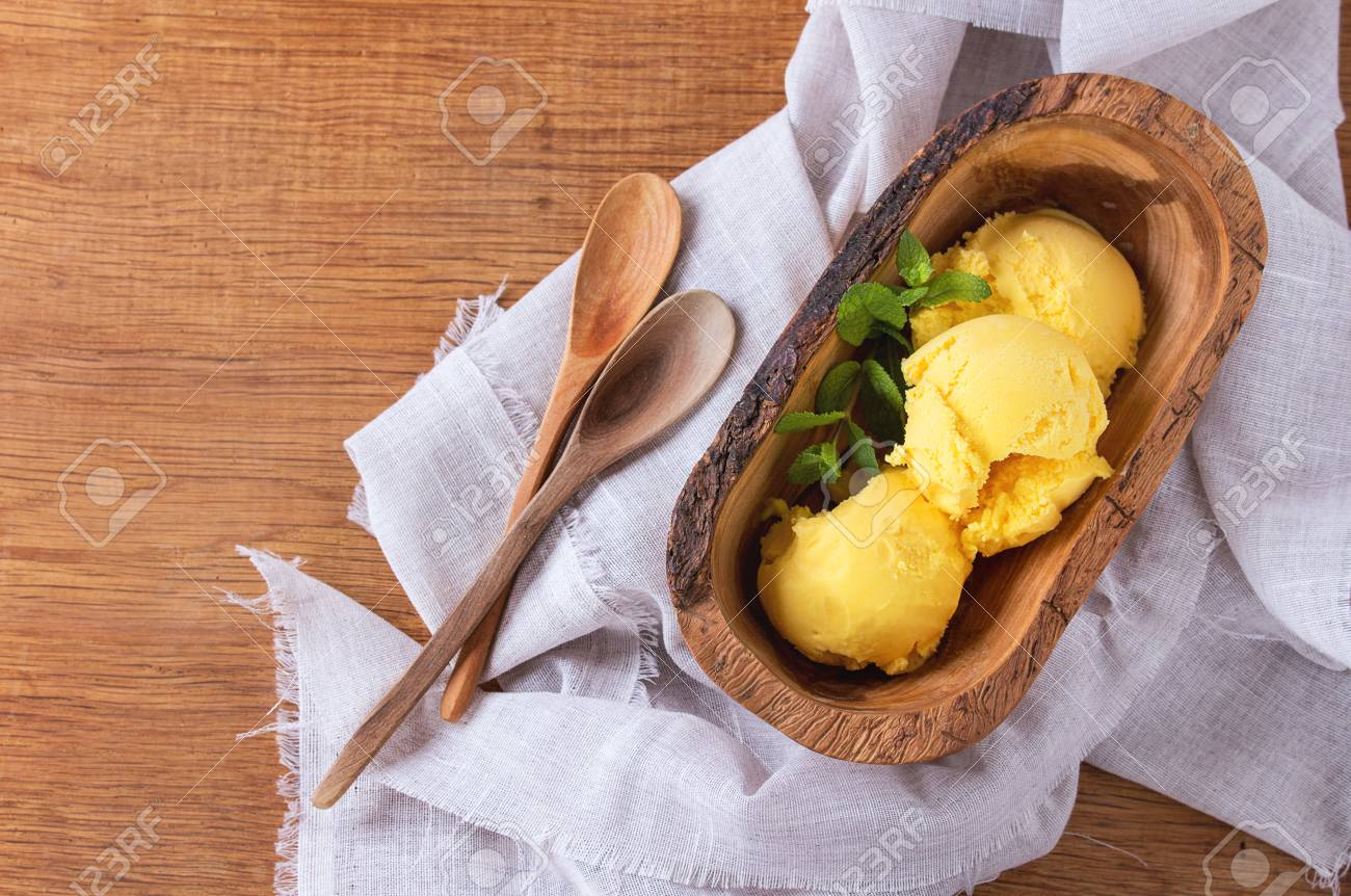Homemade mango ice cream with fresh mint in olive wood bowl with wooden spoon, served on white textile napkin over wooden textured background. Flat lay - 55783255