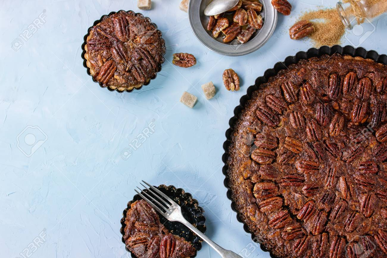 Homemade Big round caramel pecan pie and small tartlets in black iron forms, served with brown sugar, caramel sauce and vintage cutlery over blue textured background. Flat lay with copy space - 56831603