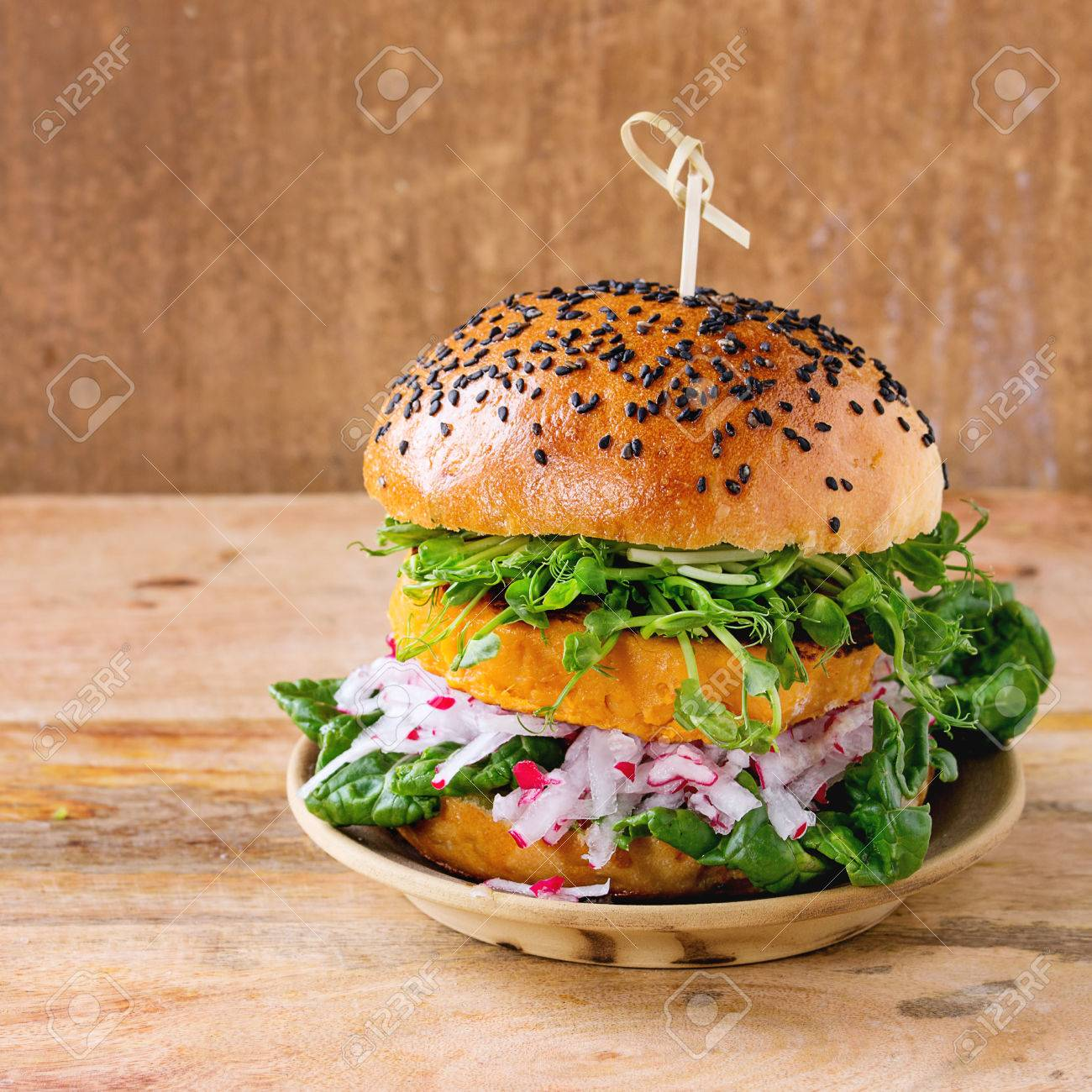 Homemade veggie sweet potato burger with fresh radish and pea sprouts served on clay plate over wooden textured background. Square image - 57591622