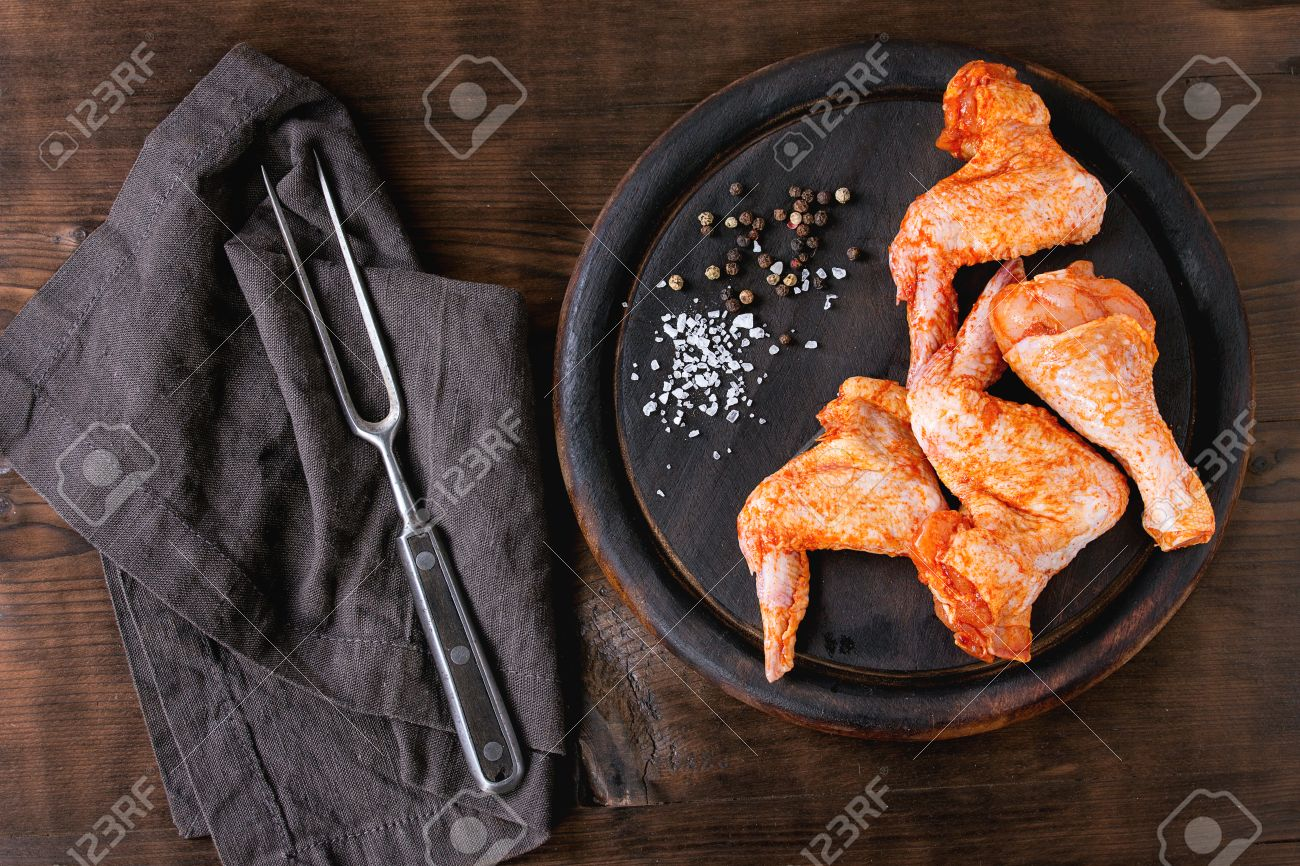 Raw Marinated chicken meat wings and legs for BBQ, served on round wood chopping board with seasoning and vintage meat fork on textile over dark wooden background. Top view with copy space. - 58525203