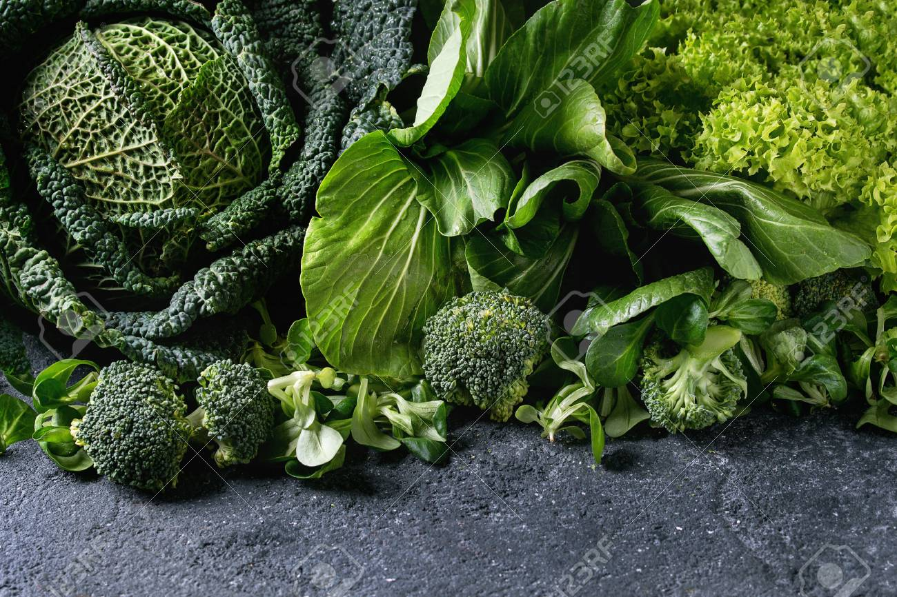 Variety of raw green vegetables salads, lettuce, bok choy, corn, broccoli, savoy cabbage as frame over black stone texture background. Space for text - 74385003