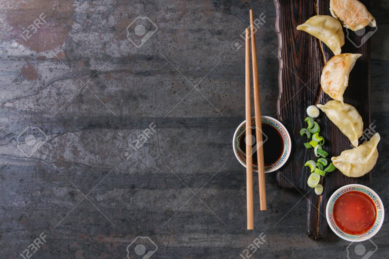 Gyozas potstickers on lettuce salad with sauces. Served in traditional china plate with chopsticks and spring onion on wood serving board over old metal background. Top view, space. Asian dinner - 74441016