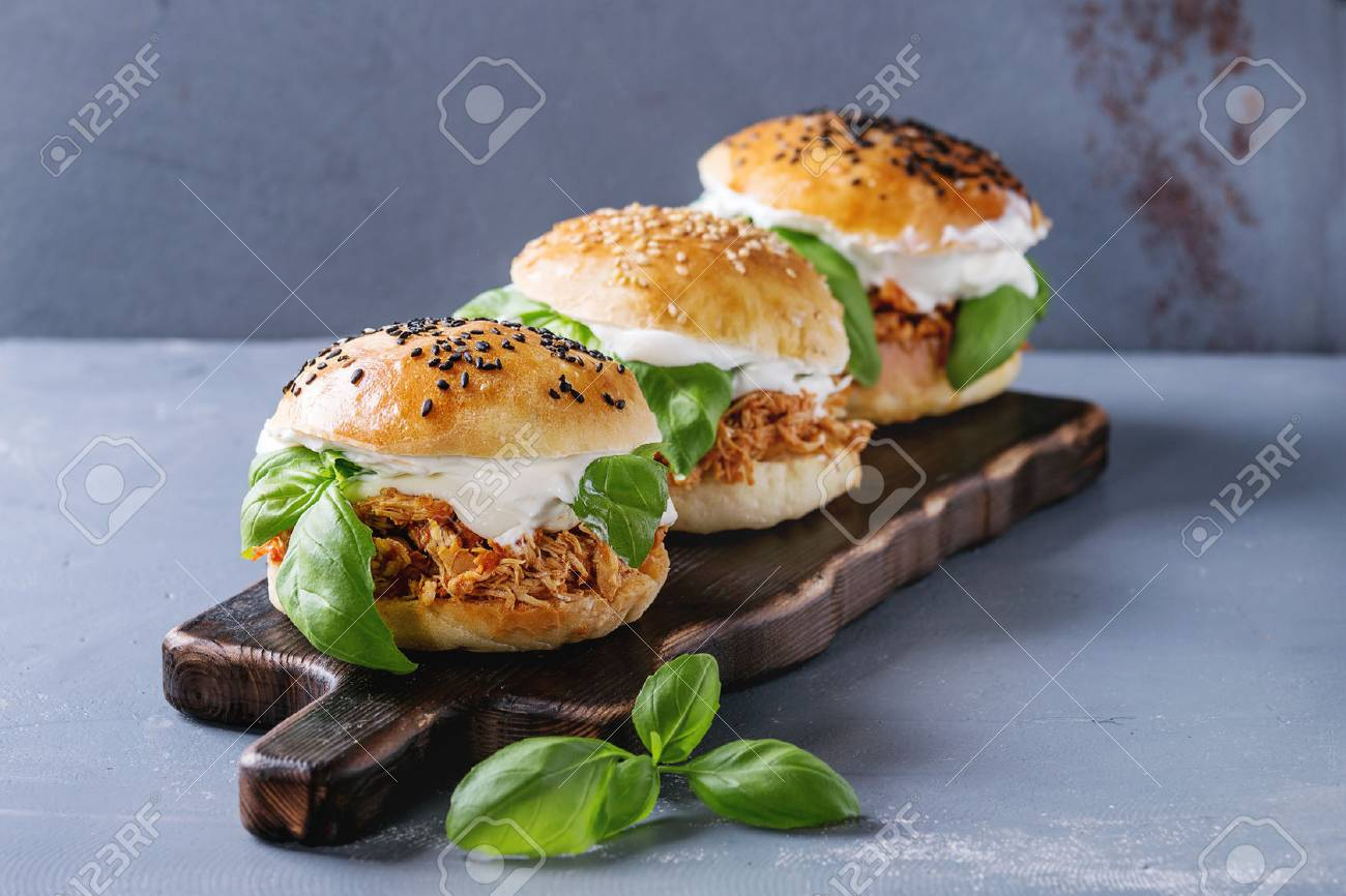 Homemade mini burgers with pulled chicken, basil, mozzarella cheese and yogurt sauce on wooden serving board over gray texture background. Healthy fast food concept - 75913287