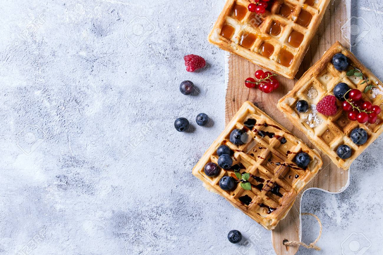 Homemade square belgian waffles with fresh ripe berries blueberry, raspberry, red currant served with caramel, balsamic sauce on wooden serving board over gray background. Top view with space - 80315791