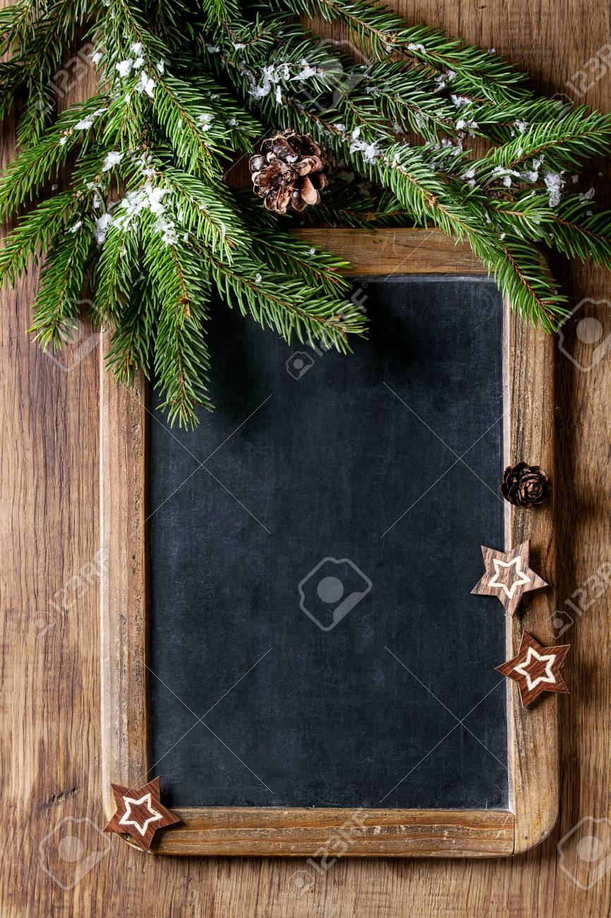 Vintage empty chalkboard with fir Christmas tree and wood modern decor stars over wooden background. Top view with space for text - 87247162