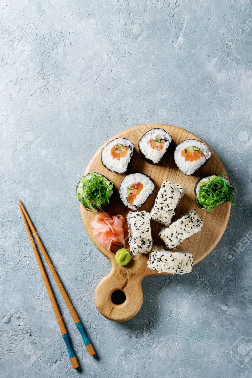 Homemade sushi rolls set with salmon, sesame seeds serving on wood serving board with pink pickled ginger, soy sauce, wasabi, seaweed salad, chopsticks on gray texture background. Top view, space - 90953093