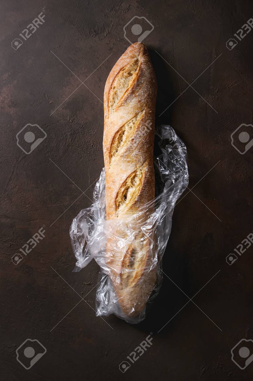 Loaf of fresh baked artisan baguette bread in plastic bag over dark brown texture background.