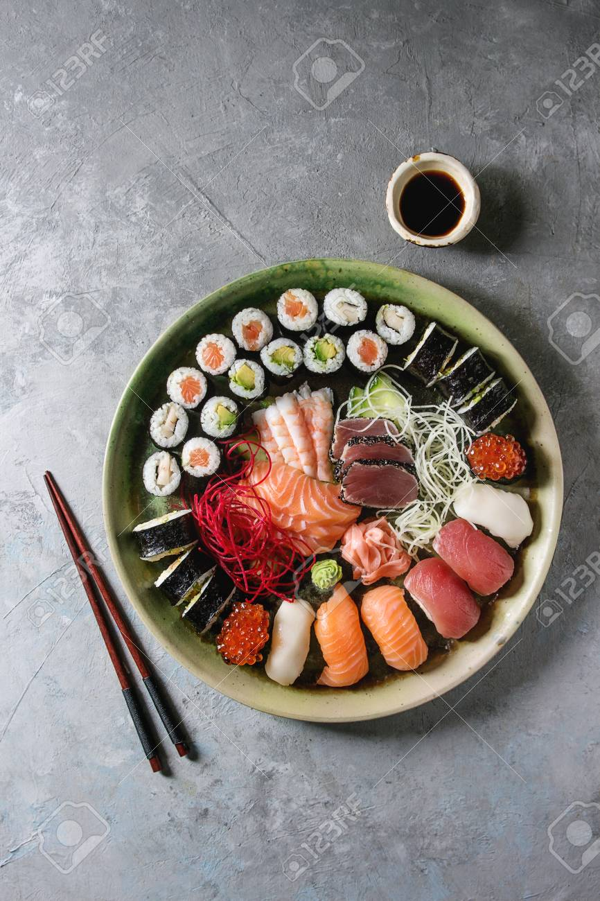 Sushi Set nigiri sashimi and sushi rolls in ceramic serving plate with salad, soy sauce and chopsticks over grey concrete background. Flat lay, space. Japan menu - 117276166