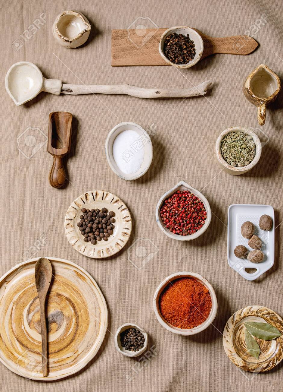 Variety of different handmade wooden and ceramic dishes, bowls and cutlery with seasonings and spices over grey linen cloth as background. Flat lay, space. Kitchen cooking concept - 136992080