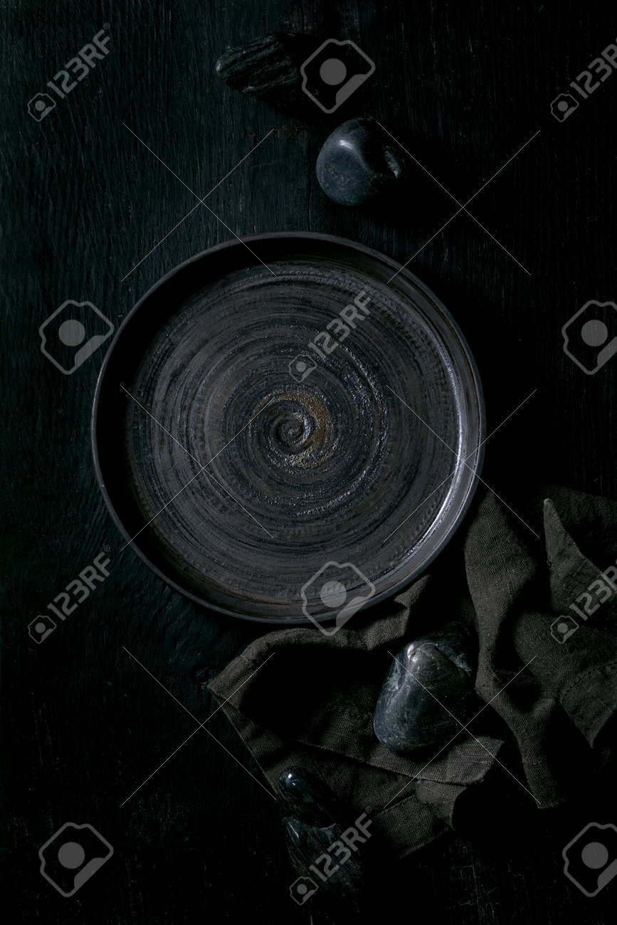 Empty black ceramic plate with black stones around on textile napkin over black wooden background. Flat lay, space. - 171172160