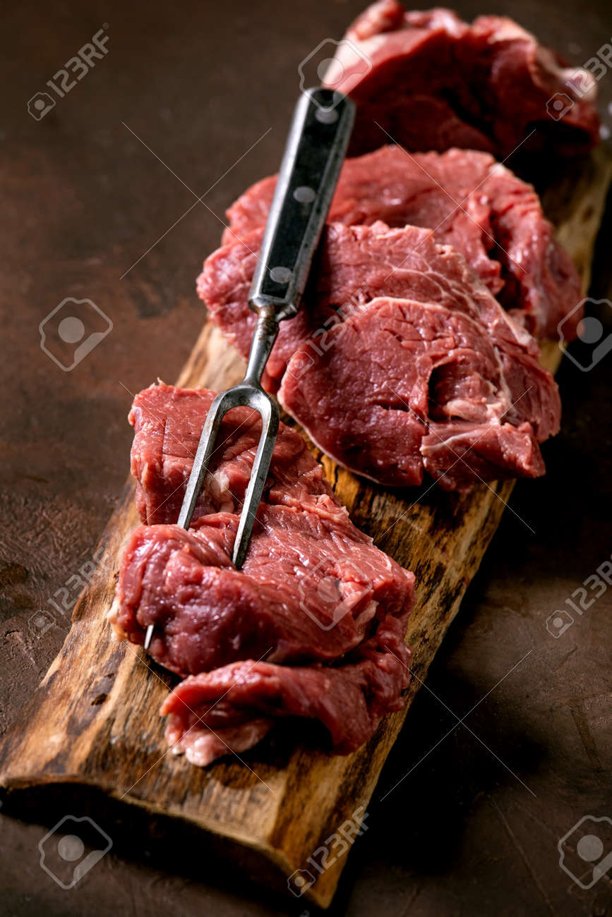 sliced raw beef tenderloin meat for steaks on wooden board with metal meat fork, salt and pepper over dark brown texture background. Food cooking background concept. Close up - 171158879