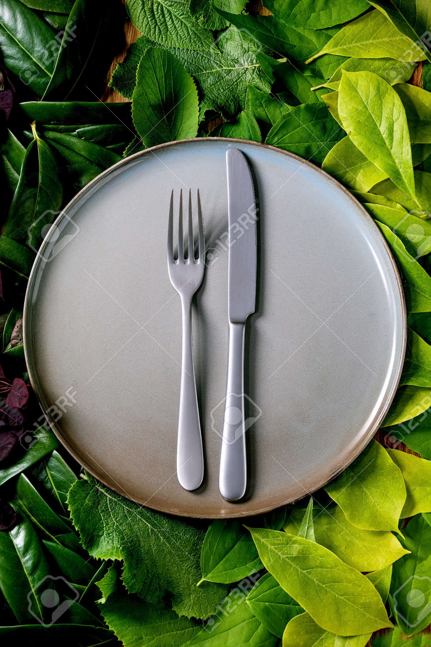Empty ceramic plate with knife and fork on background made of green leaves, green gradient. Empty place for product. Summer menu eco food concept. Nature creative layout, Top view, flat lay - 171158854