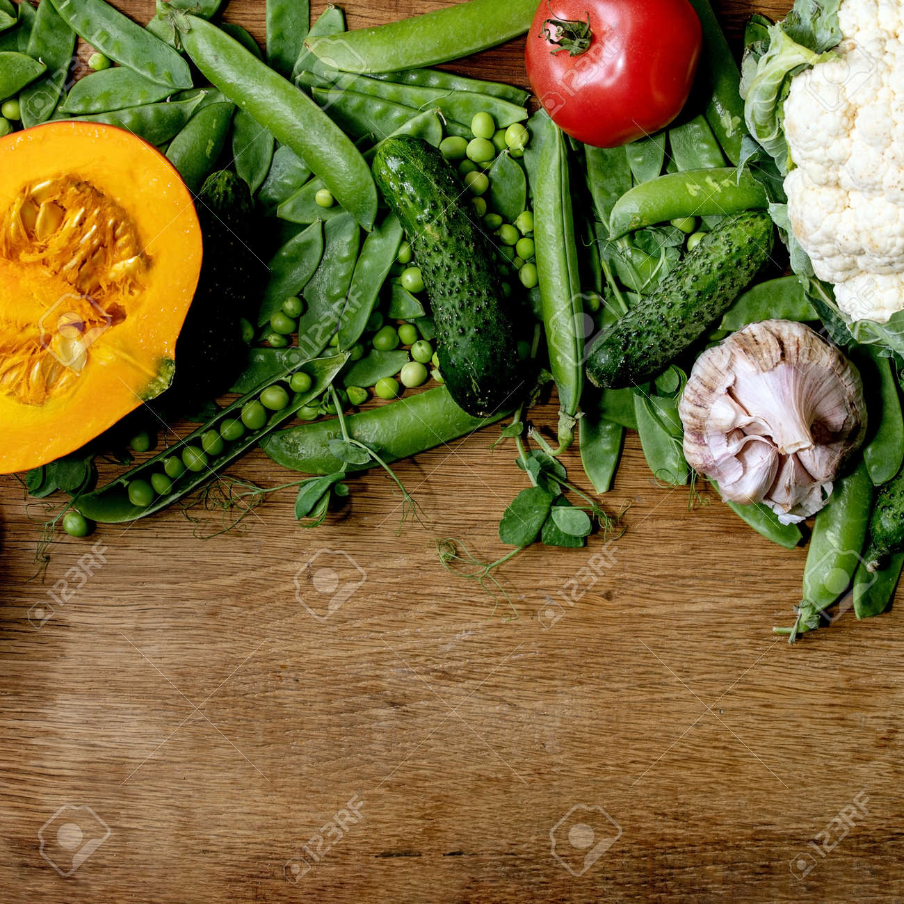 Variety of fresh raw organic vegetables for cooking. Half of hokkaido pumpkin, young green pea, cauliflower, garlic, cucumbers , tomatoes over wooden background. Farmer market concept. Flat lay, space. Square - 171903216