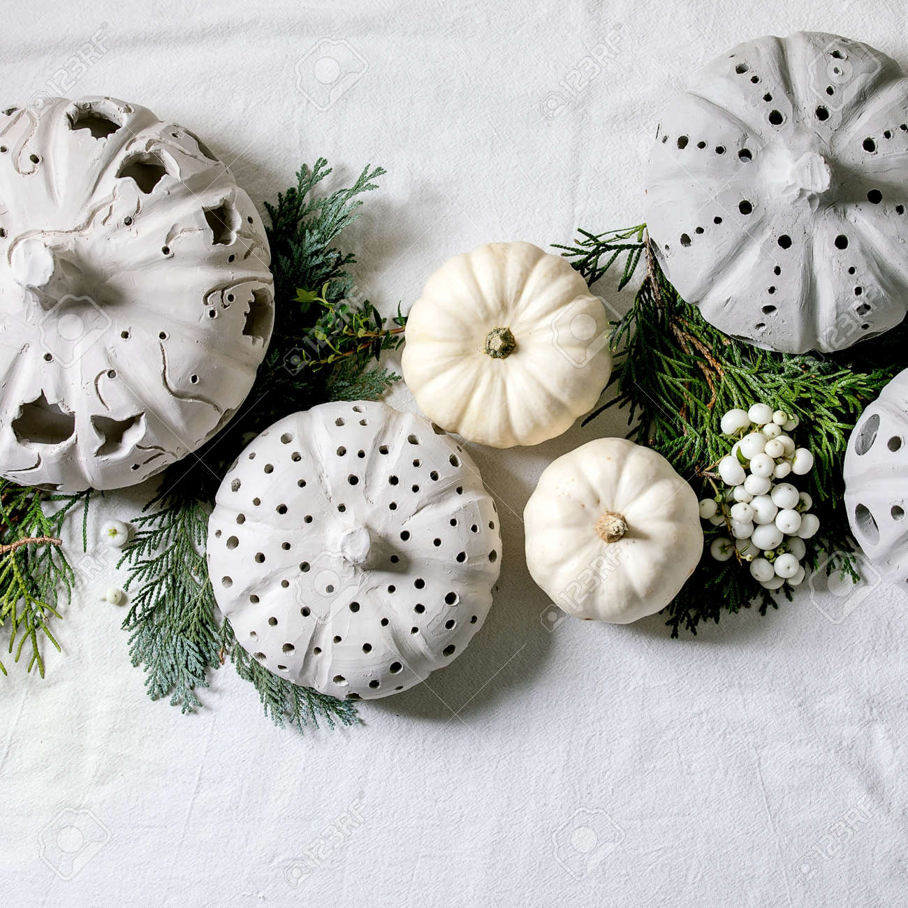 Holiday decoration with white decorative pumpkins, craft clay pumpkins, thuja branches over old wooden background. Flat lay, copy space. Square - 171902844