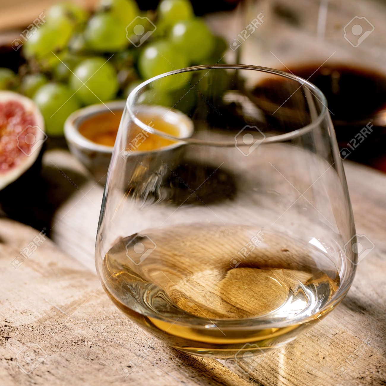 Glasses of red and white wine with grapes, figs, goat cheese and walnuts over old wooden background. Close up. Square - 172023063