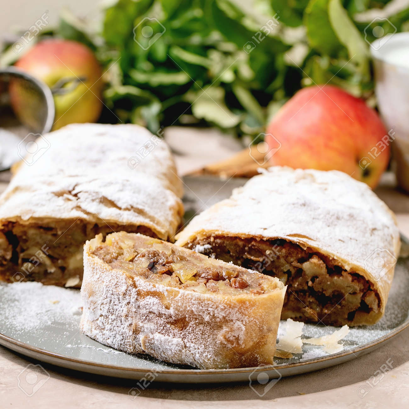 Homemade sliced classic apple strudel with icing sugar on ceramic plate with fresh apples, green leaves and cinnamon sticks above. Close up. Square - 171903383