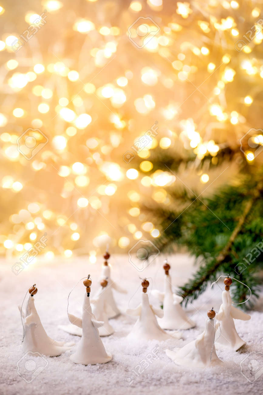 Porcelain Christmas angels. Set of craft handmade Christmas decoration on snow with bokeh holiday lights and fir tree branches. - 172023068