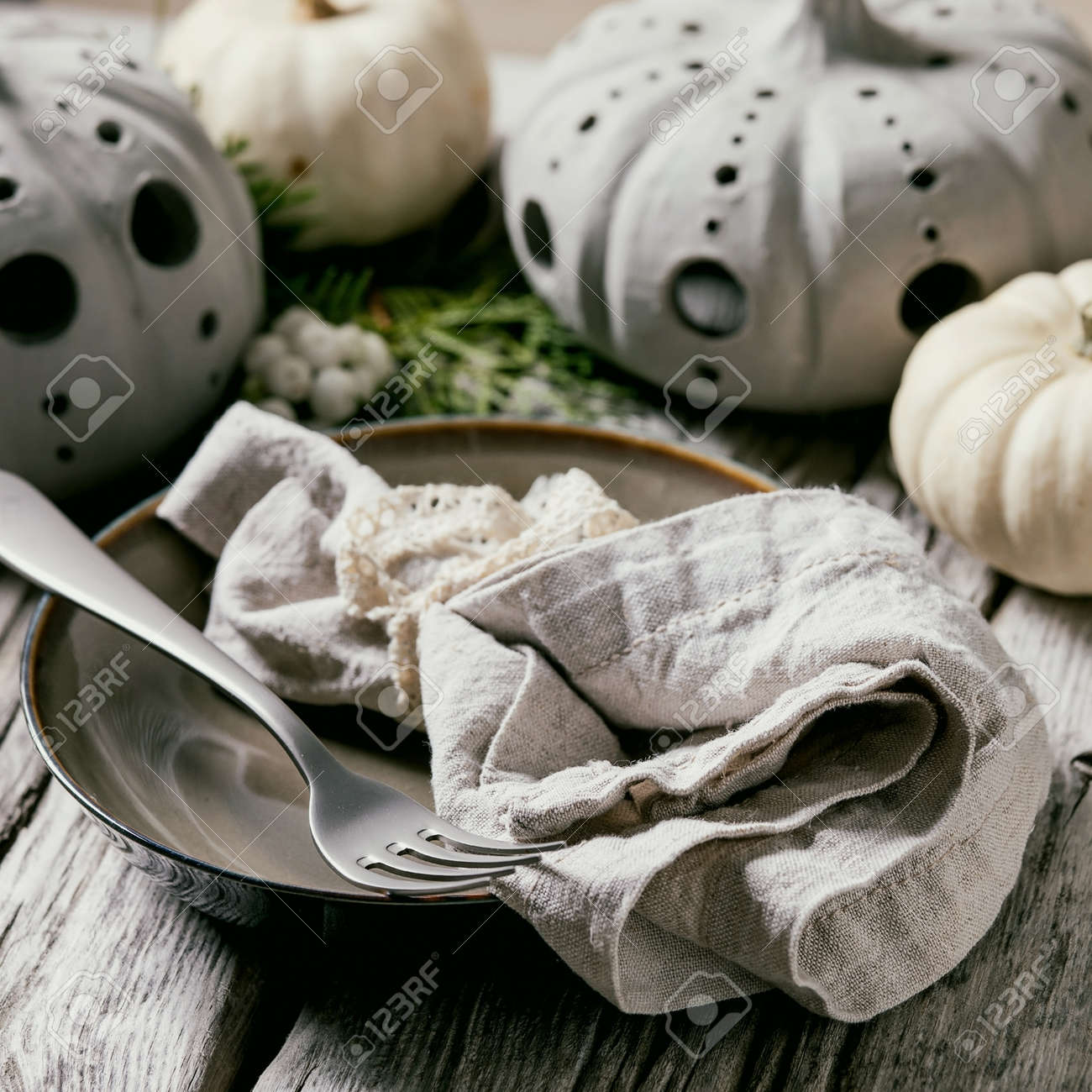 Holiday table setting decoration with white decorative pumpkins, craft clay pumpkins, thuja branches, empty plate with cloth napkin, cutlery over old wooden table. Close up. Square - 173052891