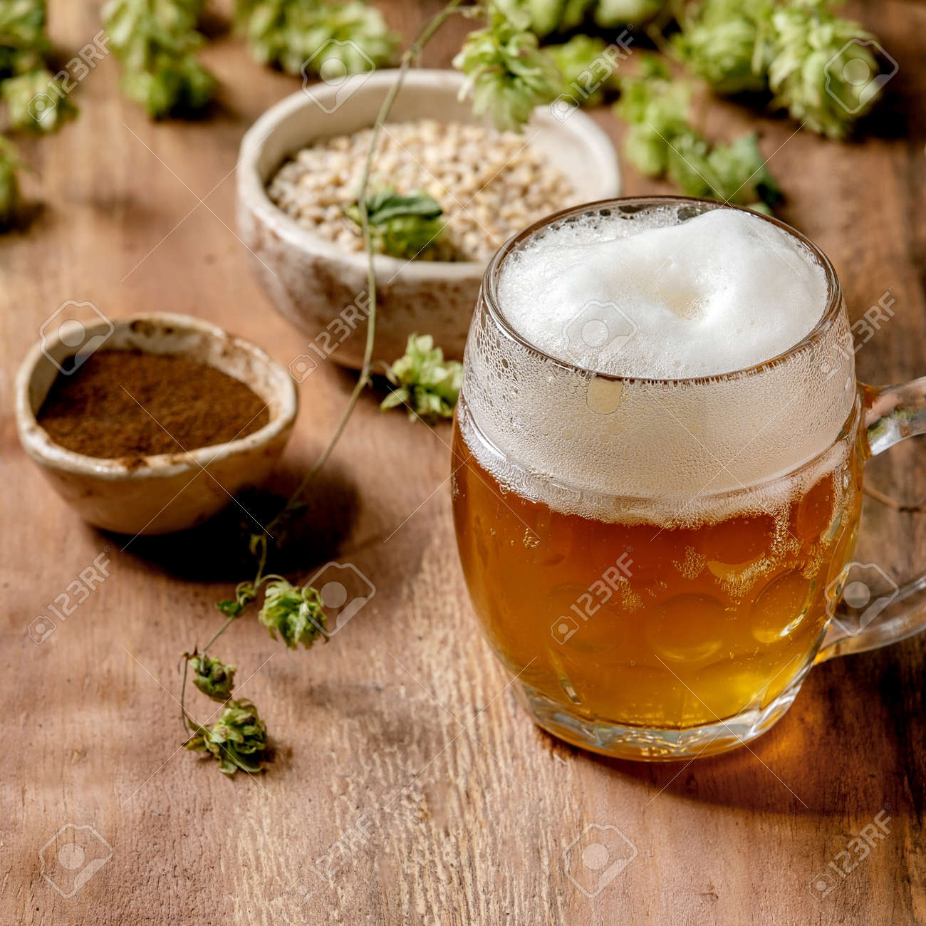 Classic glass mug of fresh cold foamy lager beer with green hop cones, wheat grain and red fermented malt in ceramic bowls behind over wooden texture background. Copy space. Square - 173054187