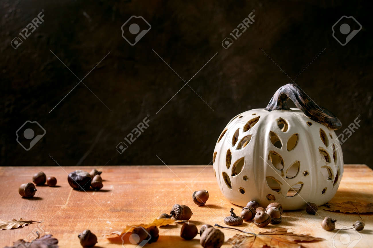 Halloween or Thanksgiving decorations, white handcrafted carved ceramic pumpkin standing on orange stone table with autumn leaves and acorns. Halloween holiday interior home decor. Copy space - 173276700
