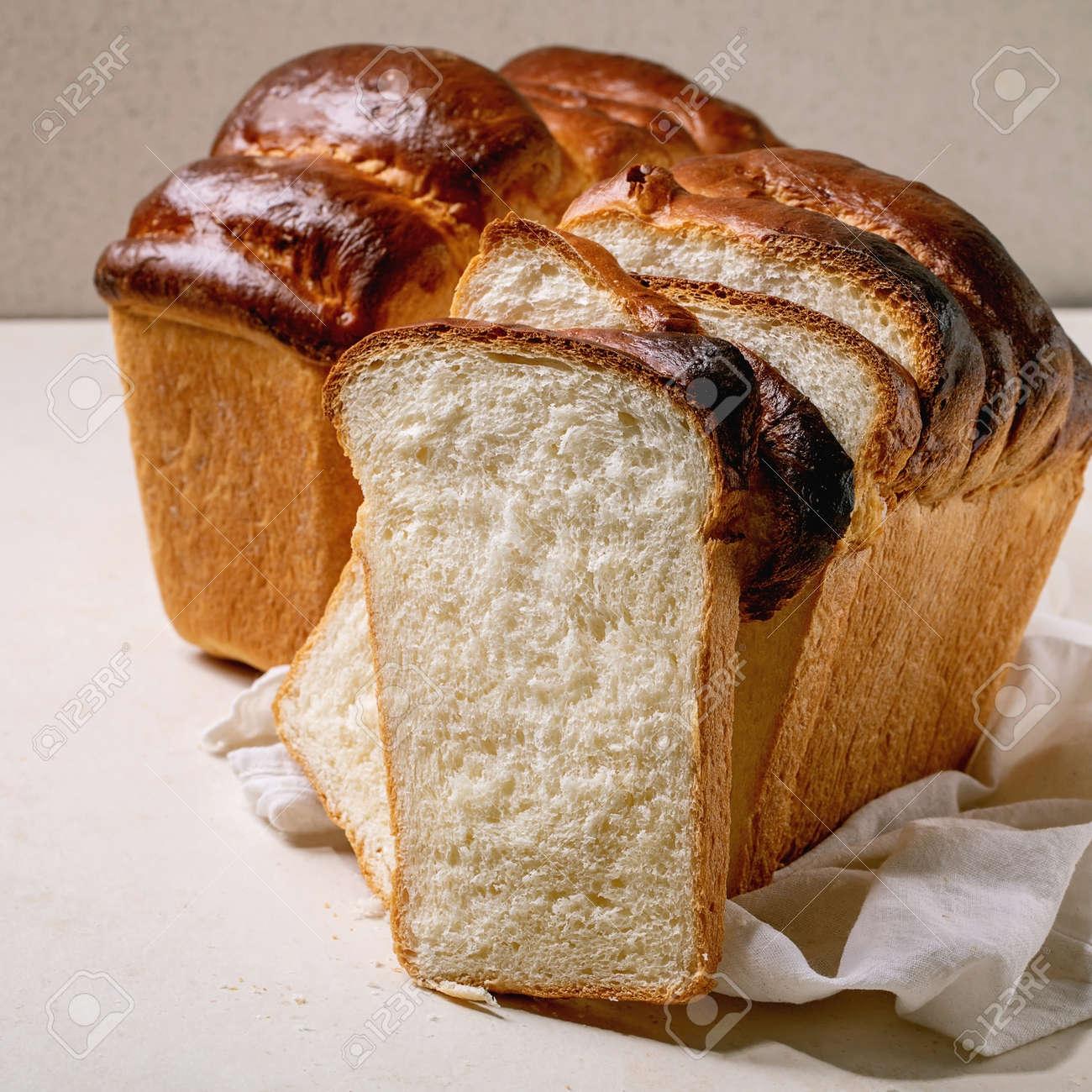 Homemade Hokkaido wheat toast bread whole and sliced on white cloth on table. Square - 173053451