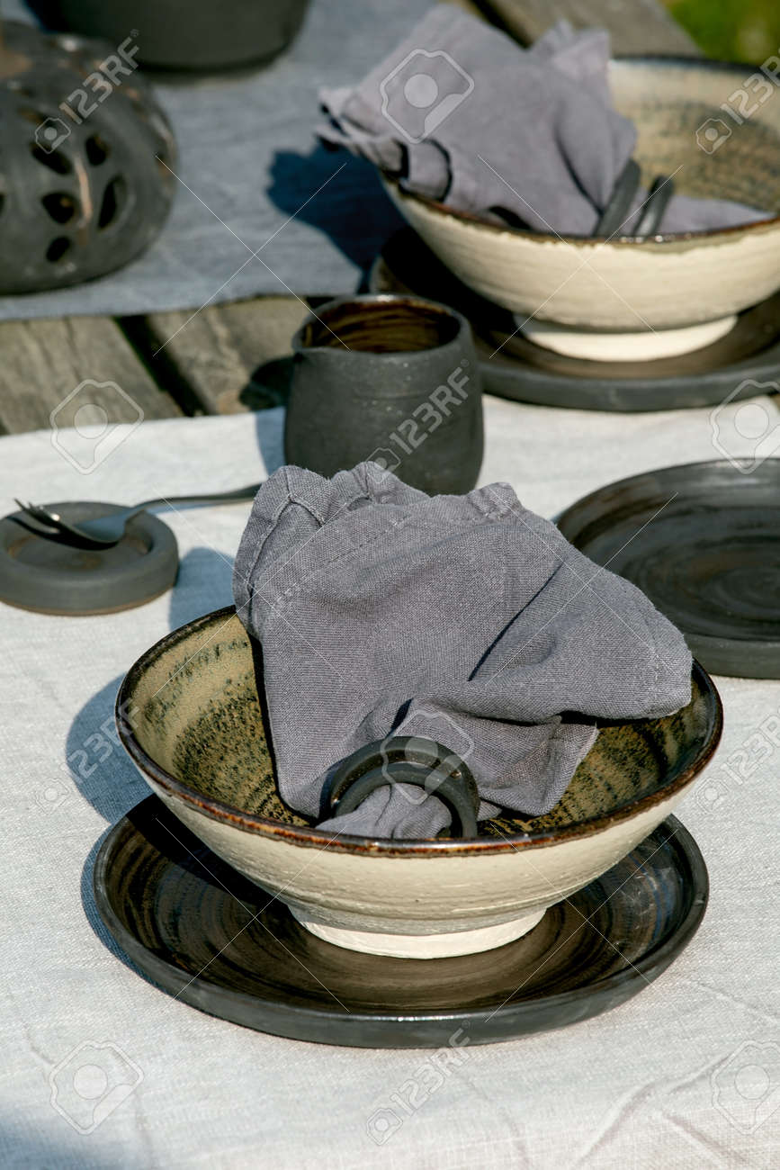 Rustic table setting outside in garden with empty craft ceramic tableware, black plates and rough bowls, pumpkin decorations, on linen tablecloth over old wooden table. Garden party. Close up - 173053509