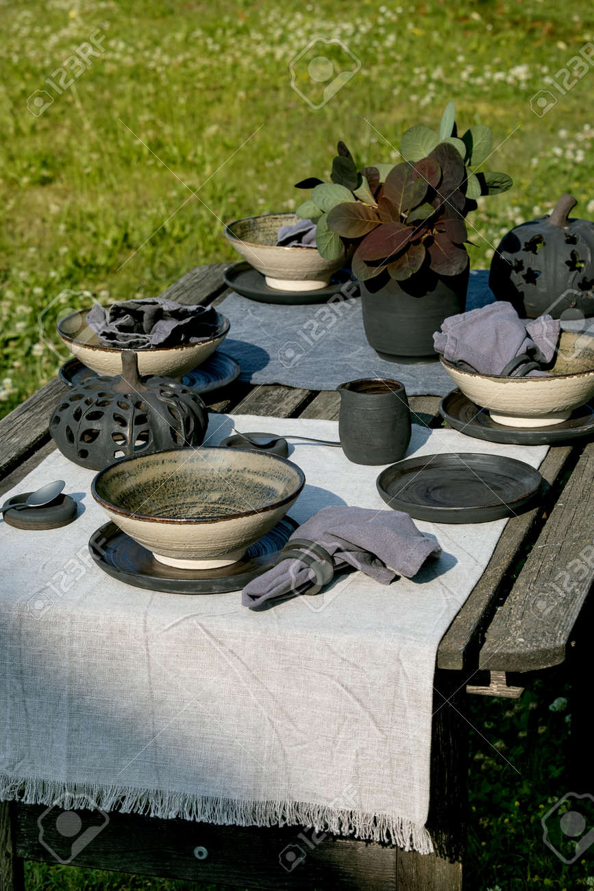 Rustic table setting outside in garden with empty craft ceramic tableware, black plates and rough bowls, pumpkin decorations, on linen tablecloth over old wooden table. Garden party - 173276705