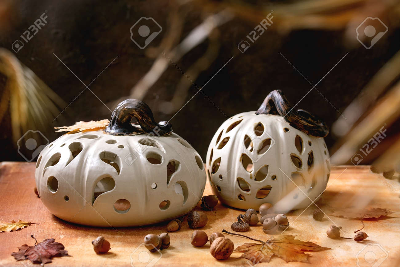 Halloween or Thanksgiving decorations, set of white handcrafted carved ceramic pumpkins standing on orange stone table with autumn leaves and acorns. Halloween holiday interior home decor - 173276706