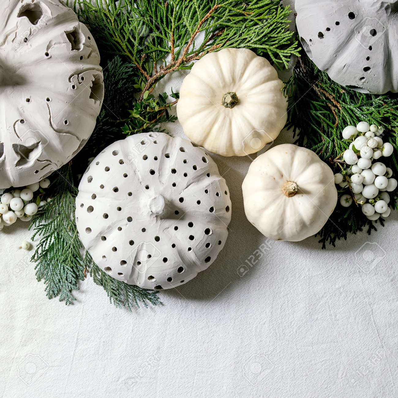 Holiday decoration with white decorative pumpkins, craft clay pumpkins, thuja branches over old wooden background. Flat lay, copy space. Square - 173053853
