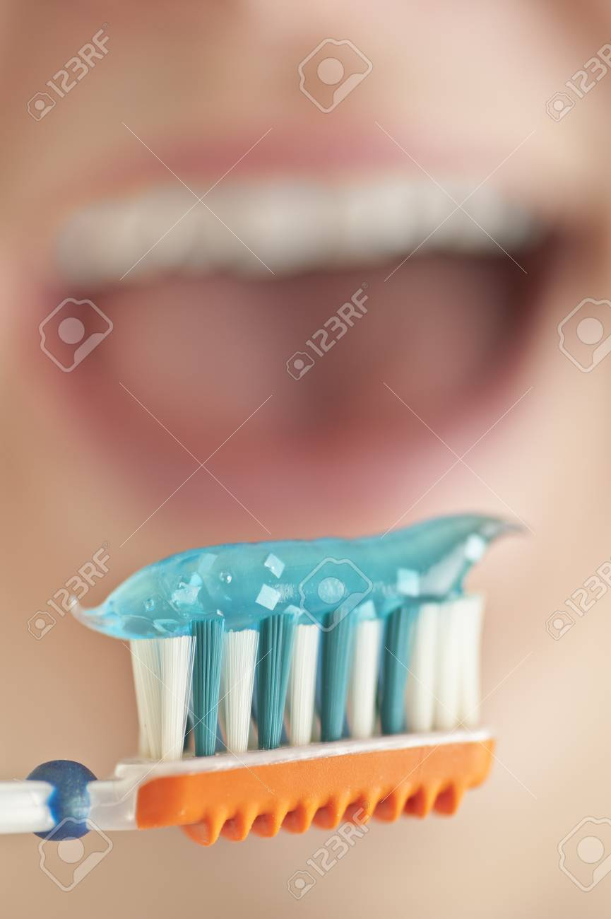 Close up of a toothbrush with toothpaste, open mouth in the background Stock Photo - 11901159