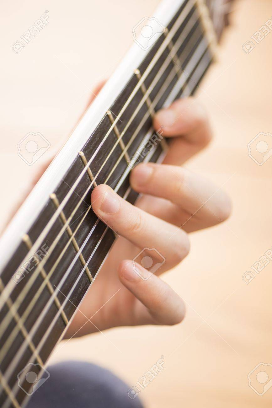 Strings And Fingers Of Young Man Playing A Chord On A Wooden Stock
