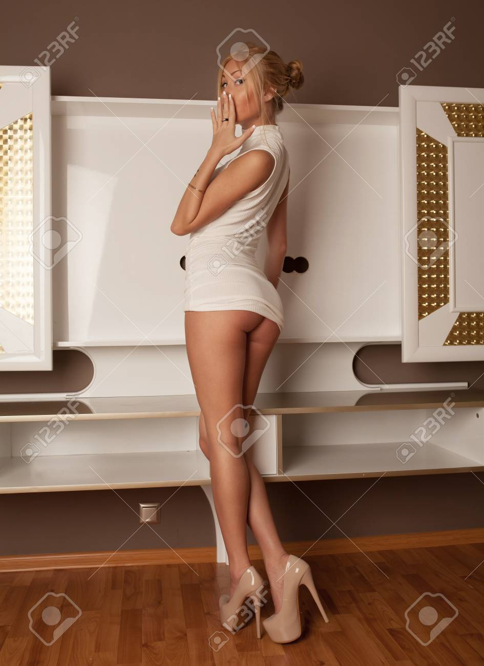 3857f863b94b Sexy blonde woman in short white dress. hot lady in her room. Stock Photo