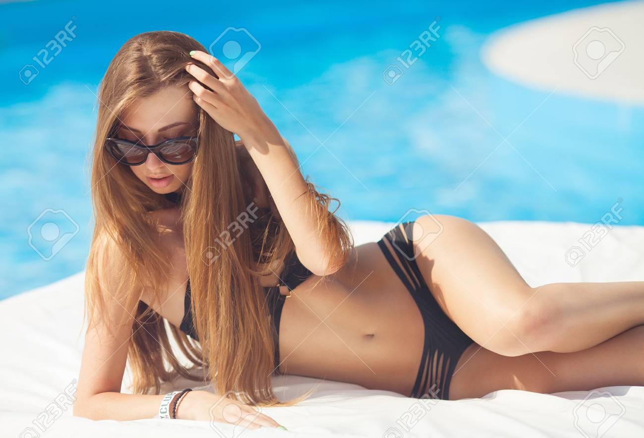 Beaux Cheveux Longs Bronzé Modèle Féminin Posant Par L eau Bleue De La  Piscine. Portrait D été En Plein Air De Fille Sexy Dans Des Lunettes De ... c57d22d8fbb