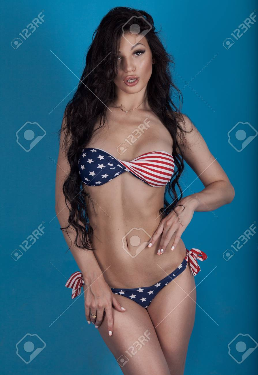 Sexy brunette woman in swimsuit with the USA flag colors on blue  background. Girl with
