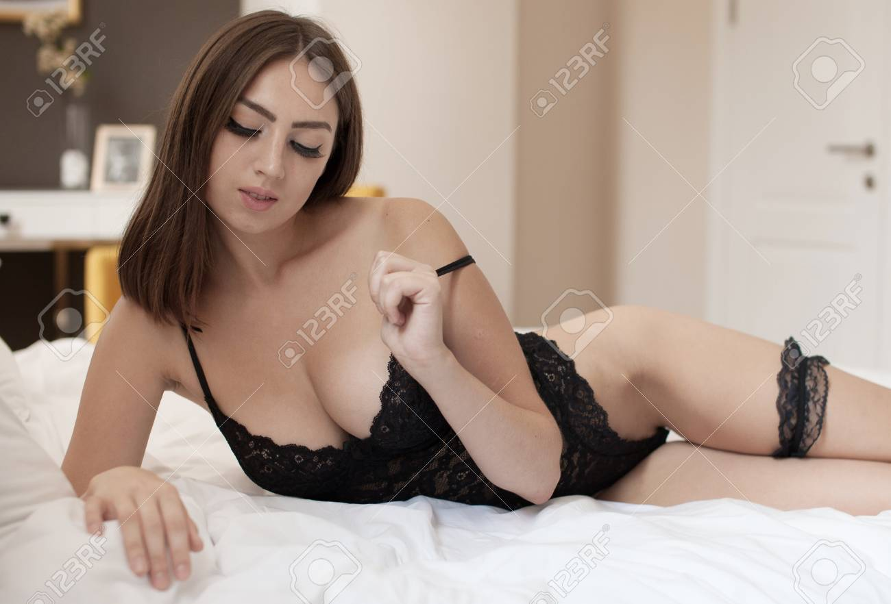 56a3cf631a2 Sensual brunette woman with long curly hair lying in white bed, posing in  sexy black