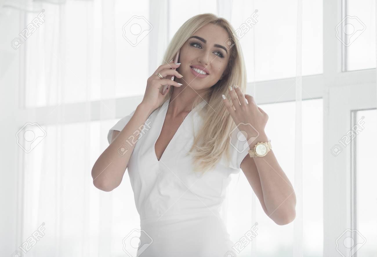 descuento en venta a pies en predominante Joven empresaria hablando por teléfono en la oficina. Sexy dama rubia con  vestido blanco.
