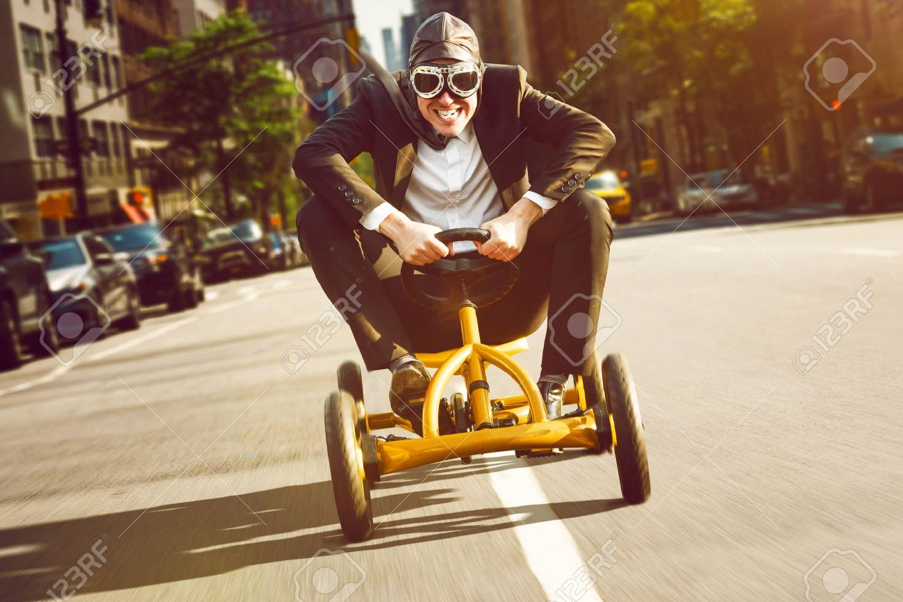 Businessman on a pedal car - 76463783